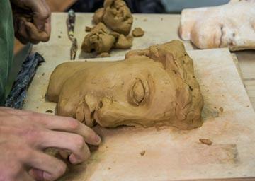 Alumno realizando unha escultura clásica en barro